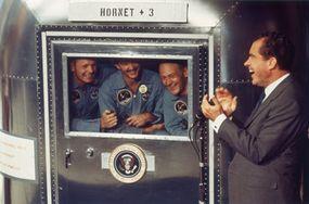 The Apollo 11 crew are quarantined upon their return to Earth. They speak with President Richard Nixon through the window of their Mobile Quarantine Facility.