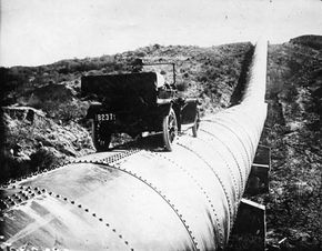 Bert Dingley drives his car along a section of the L.A. aqueduct in 1914. The massive pipes diverted water into the city.