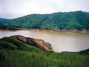 More than a week after its eruption, Lake Nyos has lost its blue hue and turned brown. You can also see vegetation damage caused by the water surge that followed the emergence of the toxic gas cloud.