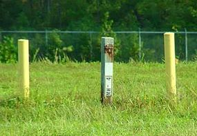 A groundwater monitoring pipe stands in the center. The two yellow markers on either side make it more visible so that equipment operators will not run into the monitoring station.