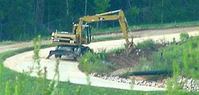 Drainage ditches run along the base of a landfill. The black pipe carries landfill gas to a pumping station.