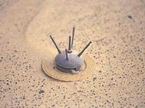 Close-up of a bounding anti-personnel mine exposed by the shifting sands of an unspecified desert