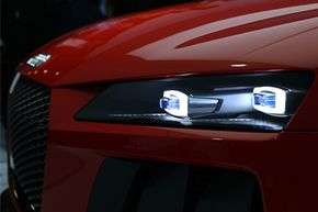 Laser headlights illuminated on an Audi quattro laserlight concept car at the Audi AG stand inside the Auto Mobil International (AMI) automotive trade fair in Leipzig, Germany.