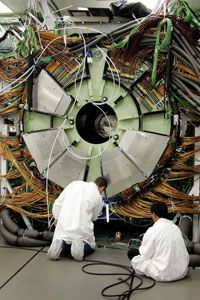 Engineers install a giant magnet inside the Large Hadron Collider, an enormous particle accelerator.