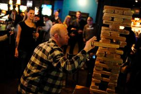 Troy Benson eases a block out an oversized Jenga game at a bar in Denver.