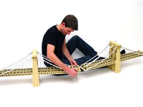 Nathan Sawaya connects two pieces of a large Lego model of the Brooklyn Bridge.