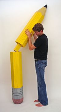 Sawaya connects two large pieces of an 8-foot pencil.