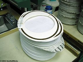 This stack of decals and back-stamps will soon be applied to a nearby stack of dishes.