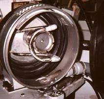The lens is ground within a rubber-lined grinding chamber. The cone-shaped quill, or grinding wheel, is at the center. The quill has a diamond cutting surface along its outer edge and is angled so only the outside edge touches the lens.