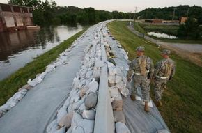 Missouri Army National Guardsmen patrol the top of a levee next to the flooding Mississippi River.