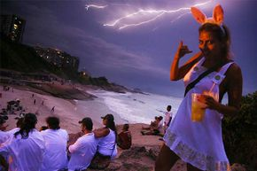 Daniela Solares walks past the camera as lightning strikes over Copacabana Beach during a Carnival festival in Brazil; she might want to take that lightning a little more seriously.