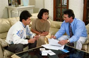 A couple listens to a pitch from an insurance salesman.