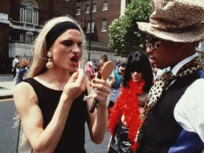 A man in drag applies lipstick at a lesbian and gay pride celebration in London, June 1995.