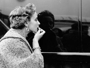 """A contestant in a """"Miss World"""" beauty competition applies her lipstick using a shiny car as a mirror, November 1953."""