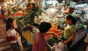 Shoppers in the Philippines peruse the produce  at a farmers' market.
