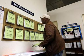 A job seeker looks at listings at a career center in Oakland, Calif.