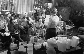 Women, some with products on their heads, attend a Tupperware party in 1950. Tupperware is one of the many successful companies that uses multi-level marketing techniques.