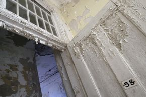 Lead paint peels from the door and walls of patient room number 58 at the Traverse City State Hospital in Michigan. The Victorian Italianate building now houses an upscale restaurant and private and commercial condominiums.