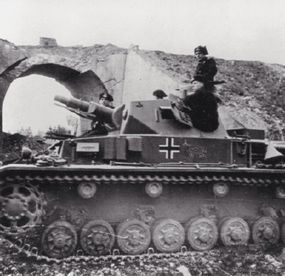 A Panzerkampfwagen IV drives through a ruined Belgian town on June 17, 1944.