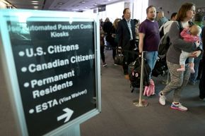 Passengers wait in line at Miami International Airport to use a new mobile app for expedited passport and customs screening. This technology is among many security advancements. It allows U.S. and some Canadian citizens to enter using their smartphones.