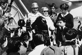 """Anita Ekberg, mobbed by paparazzi, in a scene from Fellini's """"La Dolce Vita."""""""