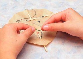Wind the paper kite's thread around the stick.