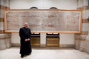 Roman Catholic Father Christopher stands in front of a replica of the Shroud of Turin in the Notre Dame de France Hospice, Jerusalem.