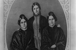 Maggie (L) and Kate (C) Fox (pictured with their older sister Leah) claimed to be mediums, but later revealed it was all a hoax.