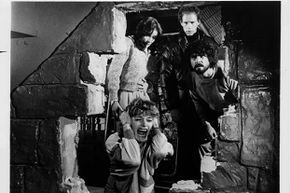Helen Shaver screams with fear while (L-R) Margot Kidder, Michael Sacks and James Brolin look through the broken wall in a scene from the 1979 film 'The Amityville Horror.' Brolin and Kidder portrayed George and Kathy Lutz.