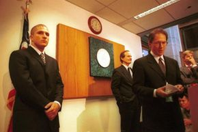 Shawn Fanning (left), founder of file-sharing service Napster, listens as his attorney David Boies (second from right) addresses a press conference regarding the company's copyright infringement woes in October 2000.