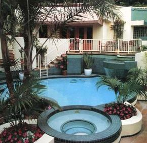 Architectural drama sets this pool and patio area apart as a true showpiece. A waterfall flows from the house to the free-form swimming pool featuring a spa.