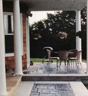 Bordered by a band of white concrete, the imprinted areas of the walkway and terrace resemble cut flagstone.