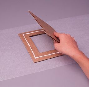 Glue a smaller piece of cardboard to the back of the frame. (Step 5)
