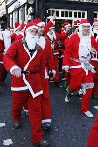 Hundreds of festive revelers dressed in Santa Claus outfits cross the road in Camden High Street on December 16, 2006 in London, England. The annual event is organized by Santacon UK.