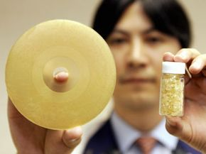 Pioneer electronics researcher Tasuo Hosoda displays a prototype model of a Blu-ray disc made of corn starch polymer. On the right are corn starch polymer pellets.