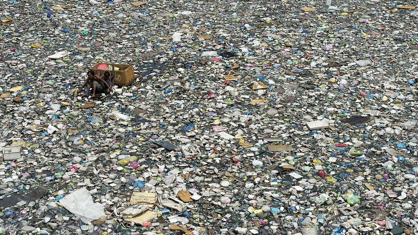 People paddle through a garbage-filled river