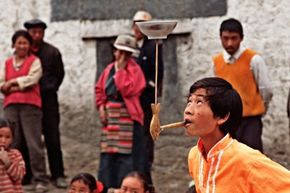 A boy in Tibet practices his plate spinning while adding a little complexity to the trick.