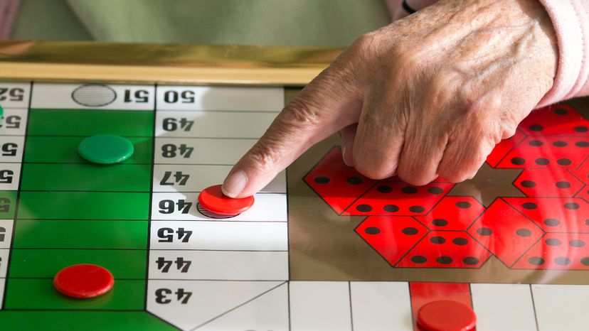 Woman playing a game of table Parcheesi