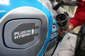 A member of the Toyota staff holds a charging plug next to a Toyota Prius Plug-in Hybrid during EV JAPAN, in Tokyo. See more pictures of plug-in hybrid cars.