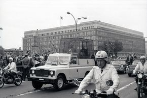 This was Pope John Paul II's second pilgrimage to Poland (in 1983). The popemobile is passing in front of the PZPR (Polish United Workers' Party) building in Warsaw.
