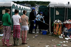 Glastonbury Festivalgoers wait for the portable toilets to be cleaned in Somerset, England.