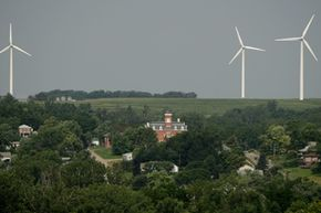 The Atchison County Courthouse is dwarfed by wind turbines in Rock Port, Mo. A wind farm consisting of four 250-foot-tall turbines provide enough energy to power the town of 1,400.