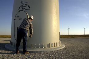Project supervisor Rusty Hurt opens a door at the base of one of the wind turbine towers in Montezuma, Kan. The wind farm contains 170 of the 289-foot-tall towers and can generate enough electricity to power 40,000 households.