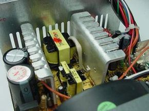 In this photo you can see three small transformers (yellow) in the center. To the left are two cylindrical capacitors. The large finned pieces of aluminum are heat sinks. The left heat sink has transistors attached to it. These are the transistors in charge of doing the switching -- they provide high-frequency power to the transformers. Attached to the right heat sink are diodes that rectify AC signals and turn them into DC signals.