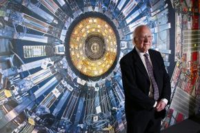 """Professor Peter Higgs stands in front of a photograph of the Large Hadron Collider at the Science Museum's """"Collider"""" exhibition on Nov. 12, 2013, in London, England."""