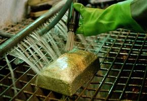 A mine worker cleans a newly poured gold bar at Driefontein Gold Mine near Carltonville, South Africa. Owning an actual gold bar is not always the best investment route. Read on to find out why.