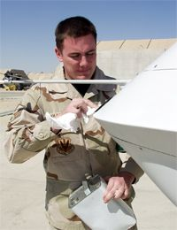 An airman cleans the lens pilots use to fly the MQ-1 Predator.