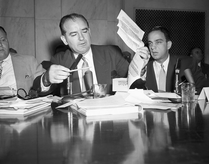 """During a House Un-American Activities Committee hearing, Sen. Joseph McCarthy holds up a letter purportedly written by FBI director J. Edgar Hoover in 1941 warning that a Fort Monmouth employee had a """"direct connection with an espionage agent."""" Attorney Roy Cohn sits beside McCarthy. Bettmann/Getty Images"""