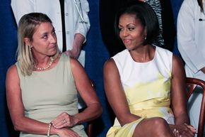 First Lady Michelle Obama sits with Maggie Roberts at the event announcing the new preventive care regulations. Ms. Roberts' son was diagnosed with cancer at a well-baby visit; twelve years later, he is in remission. See more staying healthy pictures.