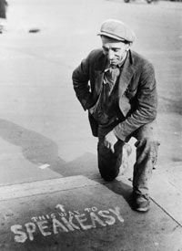 A man checks out a sidewalk sign pointing the way to an illegal speakeasy.